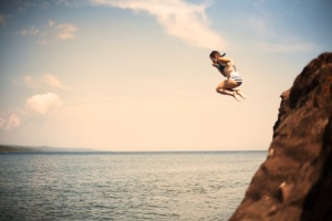 Young Girl Jumping Off Cliff Into Water